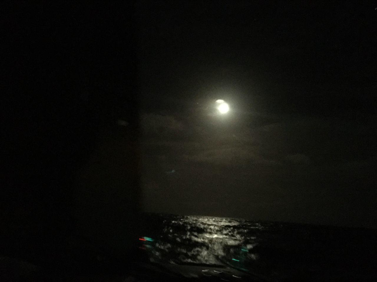 VIEW OF SEA AGAINST MOON IN SKY