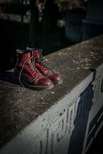 Close-up of shoes on retaining wall