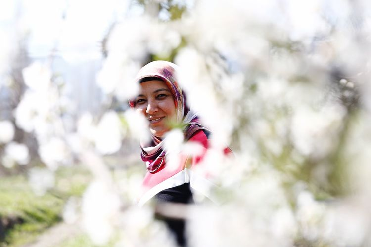 woman among the cherry blossoms Real People One Person Smiling Lifestyles Leisure Activity Day International Women's Day 2019 Young Adult Happiness Plant Women Nature Front View Young Women Clothing Portrait Tree Casual Clothing Emotion Selective Focus Outdoors