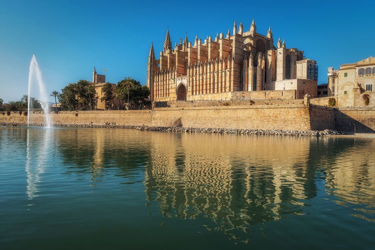 La Seu during a sunny day Water Architecture Reflection Built Structure Building Exterior Waterfront Sky History Nature The Past Travel Destinations Building Clear Sky Day No People Travel Tourism Tree Outdoors Mallorca SPAIN Pont EyeEm Best Shots Water Reflections Cathedral