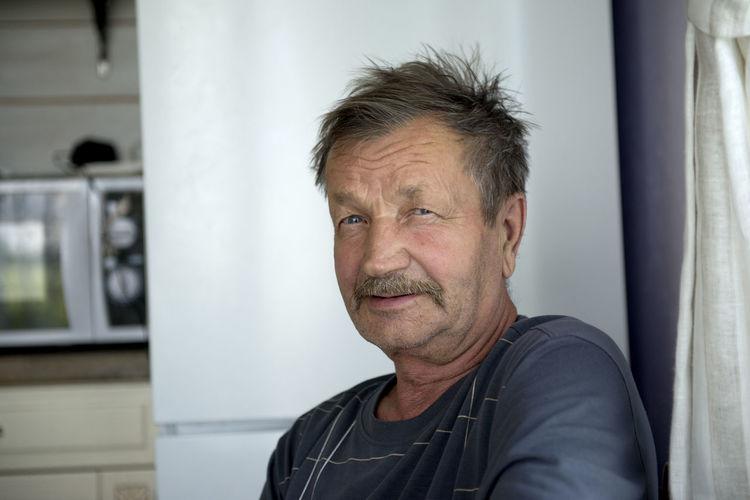Portrait of senior man sitting at home