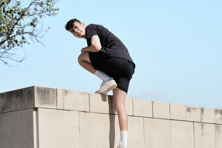Low angle view of young man against wall