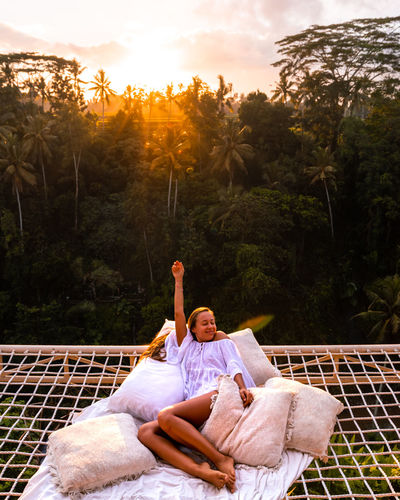 A girl lying in a net in the morning above the jungle in bali
