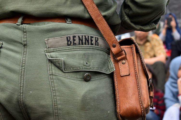 Midsection of man with brown shoulder bag