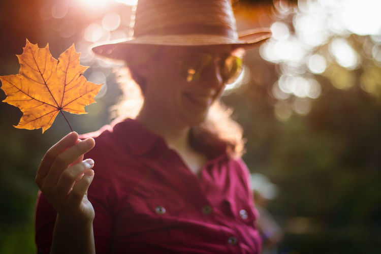 Autumn Fall Colors Autumn Beauty In Nature Close-up Day Fall Focus On Foreground Holding Leaf Lens Flare Lifestyles Nature One Person Outdoors People Person Real People Smiling Sun Sunlight Sunset Women Young Adult Young Women