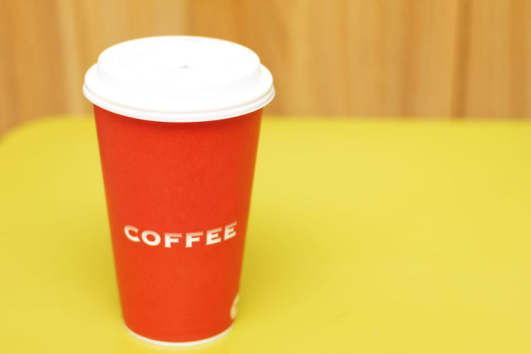 Close-Up Of Coffee Cup On Yellow Table