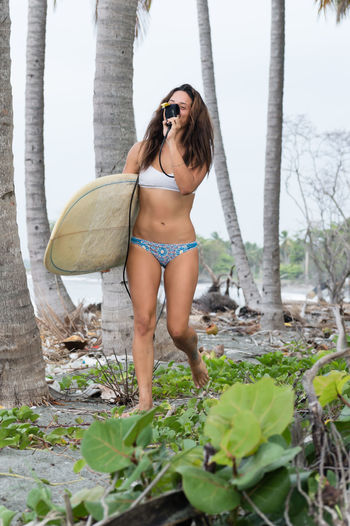Woman with surfboard walking in forest
