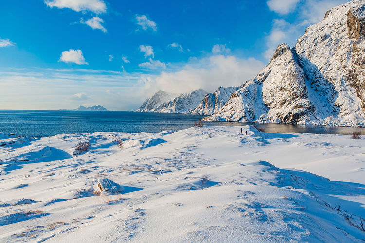 Scenic view of snowcapped mountain by sea against sky