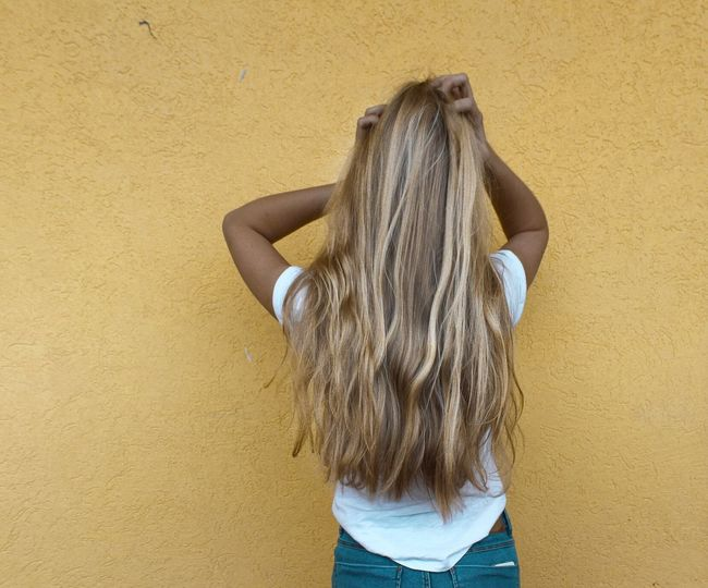 Rear View Of Young Woman Standing With Hand In Hair Against Yellow Wall