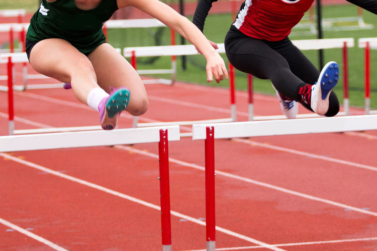 Female athletes hurdling on sports track