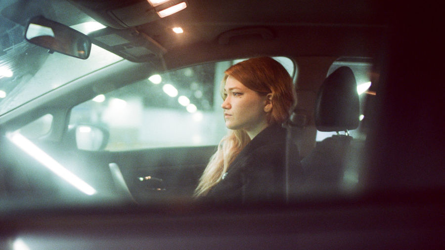 Portrait of young woman looking through car window