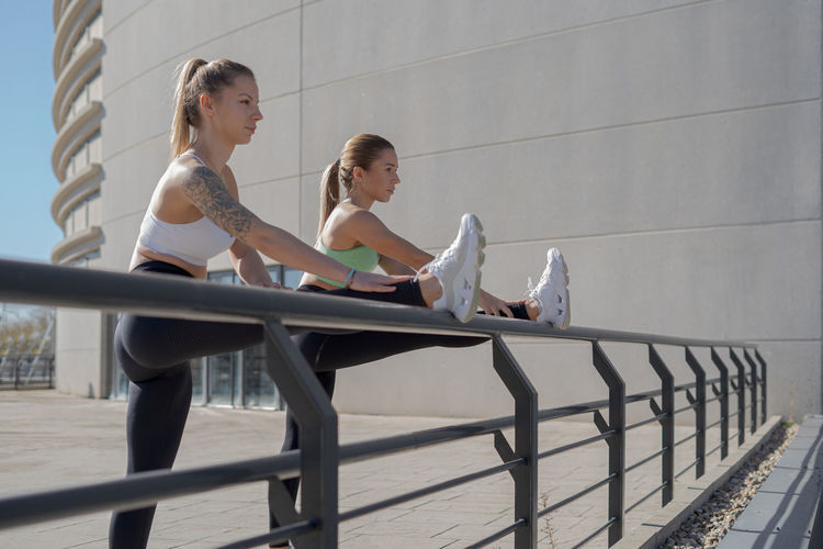 Side view of women sitting on railing