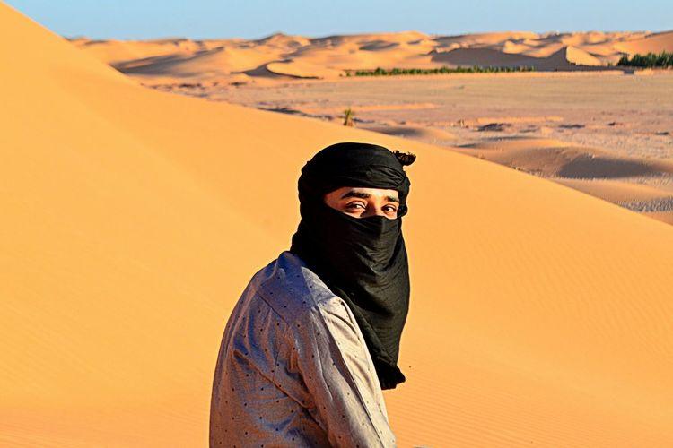 Mid adult man in desert against sky