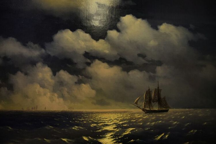 Boat sailing in sea against storm clouds