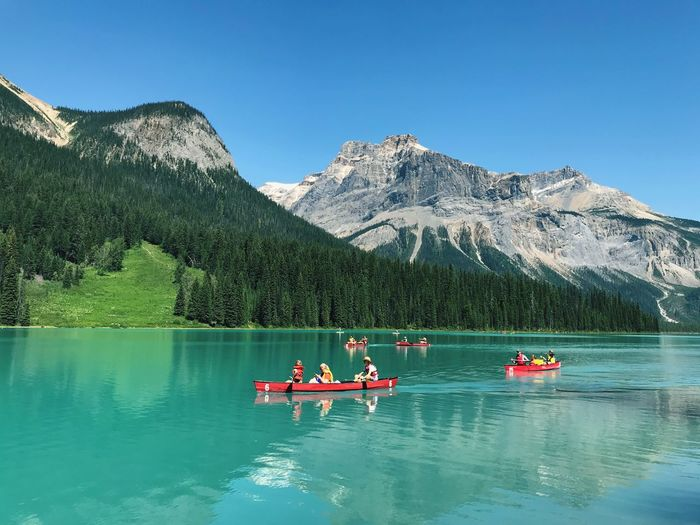 People In Boat On Lake Against Mountain Range