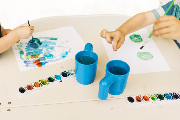 High angle view of baby hand holding painting