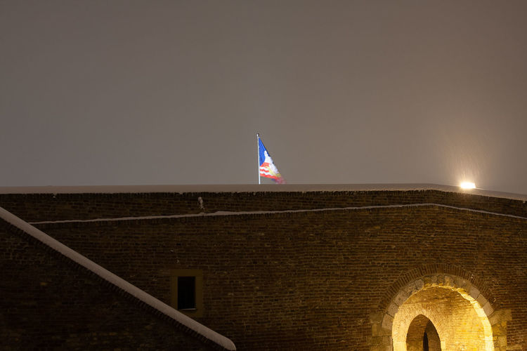 Low angle view of flag on building against sky at night