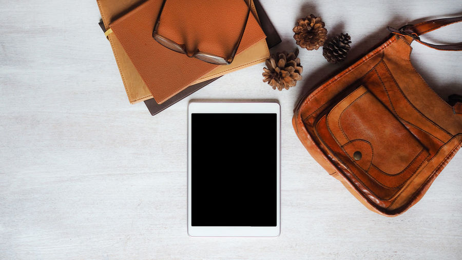 Place of work, black blank digital tablet, old book stack and vintage leather bag on white color wood background, vintage color tone process for business and education technology concepts Still Life No People Directly Above Table Wood - Material Book Indoors  Publication Brown High Angle View Wireless Technology Paper Pen Technology Smart Phone Copy Space Portable Information Device Writing Instrument Diary Communication Blank Leather Workplace Vintage Style Education