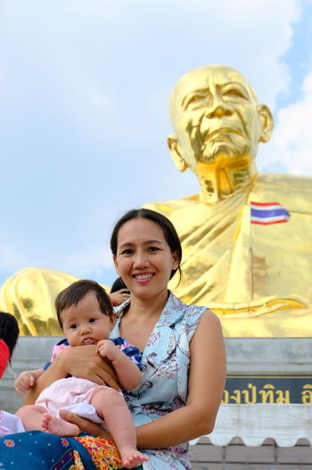 Portrait of mother and daughter in front of budhist temple and the thai flag