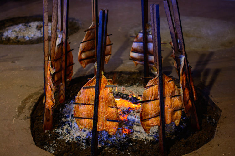Close-up of salmon tied to stick at bonfire