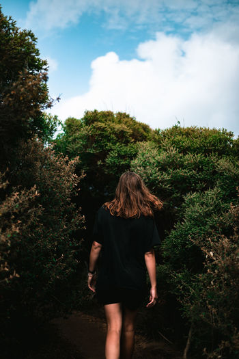 Rear view of woman standing by plants against trees