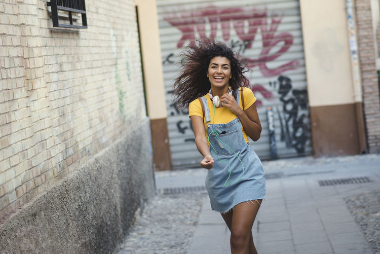 beautiful african girl with headphones walking happy in the street Architecture Beautiful Woman Building Exterior Built Structure Emotion Hair Hairstyle Happiness Leisure Activity Lifestyles Looking At Camera One Person Outdoors Portrait Real People Smiling Three Quarter Length Women Young Adult Young Women
