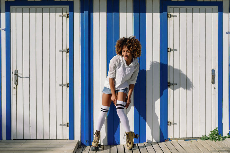 Young black woman on roller skates near a beach hut. Girl with afro hairstyle rollerblading on sunny promenade. Full Length One Person Curly Hair Front View Day Architecture Young Adult Hairstyle Sunlight Adult Portrait Casual Clothing Standing Women Brown Hair Serious Outdoors Occupation Hair Beautiful Woman