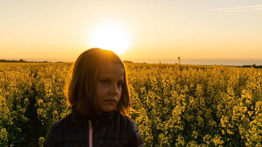the Sun goes down with a Dream of the Girl Agriculture Beauty In Nature Farm Field Flower Growth Headshot Land Landscape Leisure Activity Lens Flare Lifestyles Nature One Person Outdoors Plant Portrait Portrait Photography Real People Scenics - Nature Sky Standing Sun Sunset Yellow
