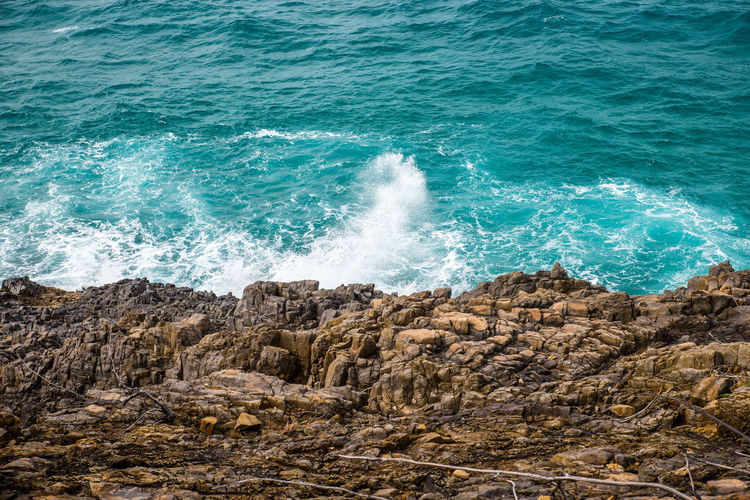 High angle view of waves splashing on rock in sea