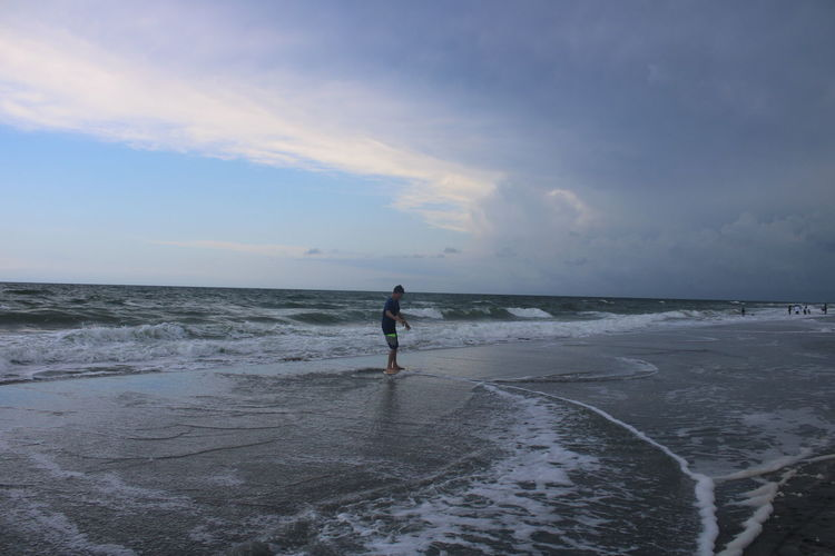 Man standing on beach against  dramatic evening sky