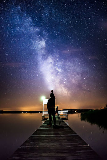 Silhouette man standing on pier against sky at night