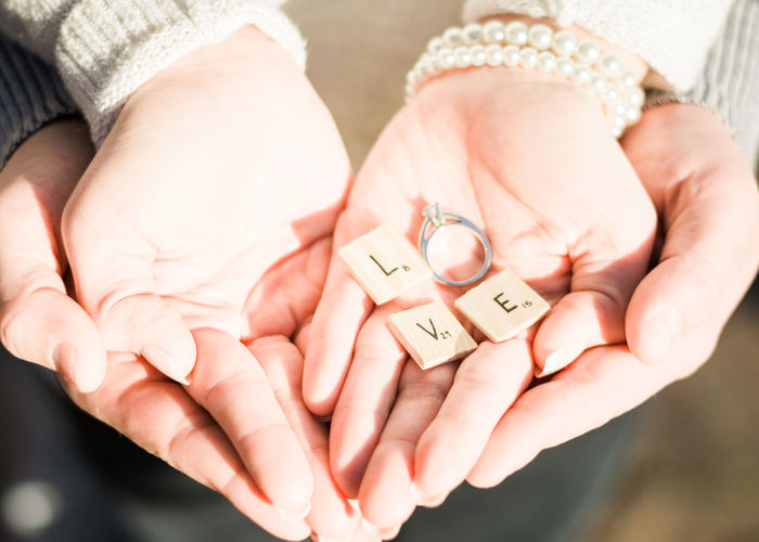 Cropped image of couple hands holding engagement ring with letter blocks