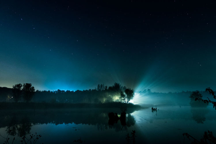 Reflection Of Silhouette Trees On Calm Lake Against Star Field
