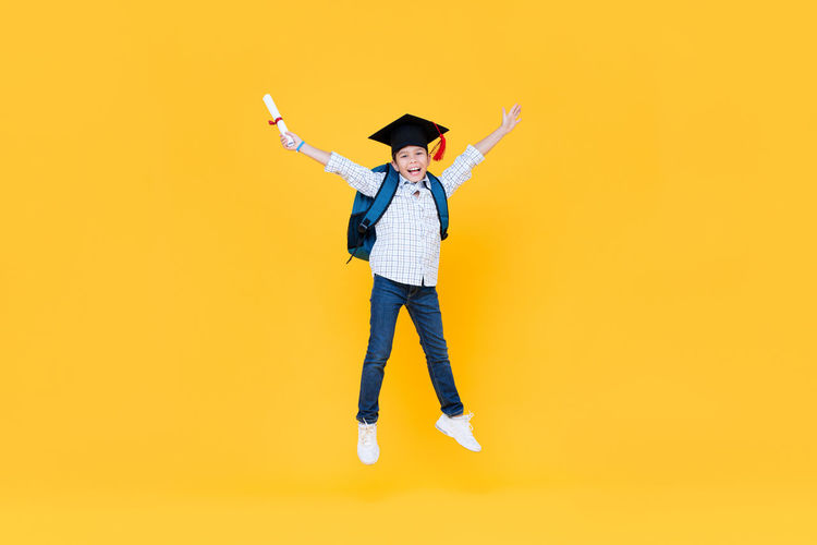 Cheerful boy against yellow background