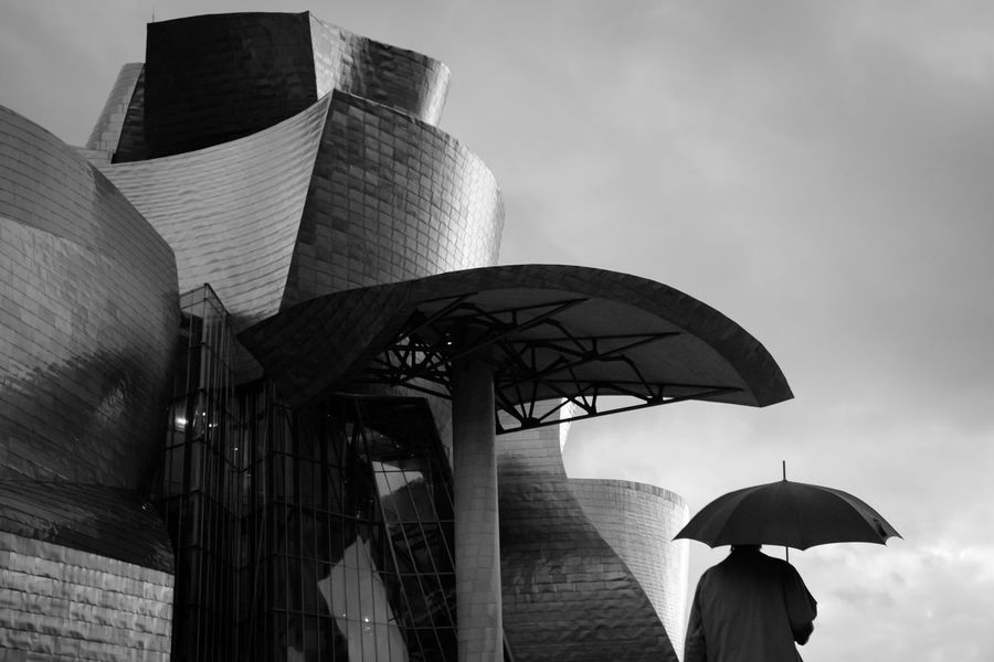 urban shapes • Sinuous Sinuosity Curves And Lines Sinuous Curves Smooth Texture Urban Urban Geometry Guggenheim Bilbao Rainy Rainy Day Architecture Built Structure Outdoors One Man Only Solitary Discreet Photography From Behind Fuji X Series FUJIFILM X-T10 The Week On EyeEm Geometric Shape Sunset Sunset Silhouettes Black And White Friday The Graphic City The Architect - 2018 EyeEm Awards The Street Photographer - 2018 EyeEm Awards