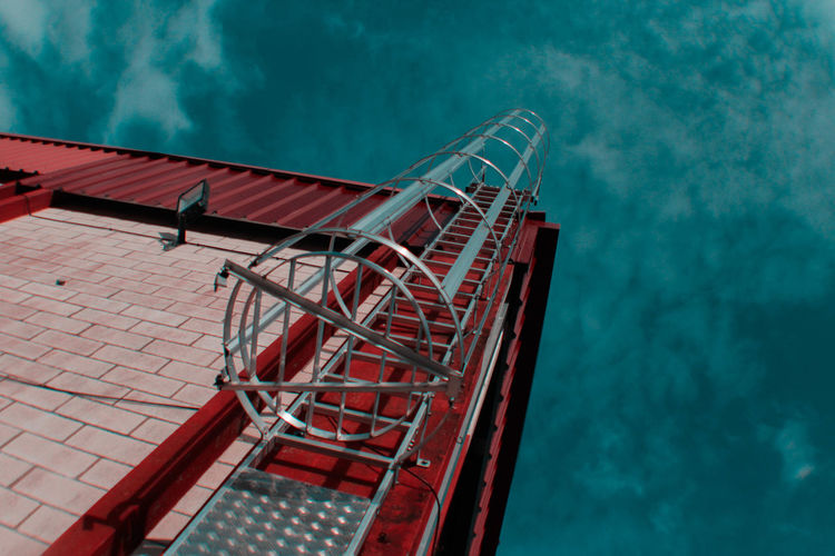Low angle view of metal frame against blue sky