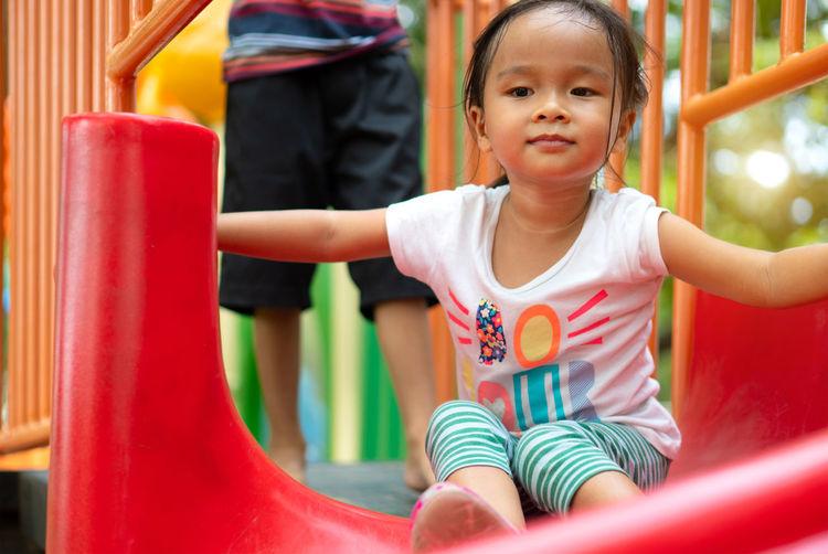 Full length of cute girl sitting on slide in playground