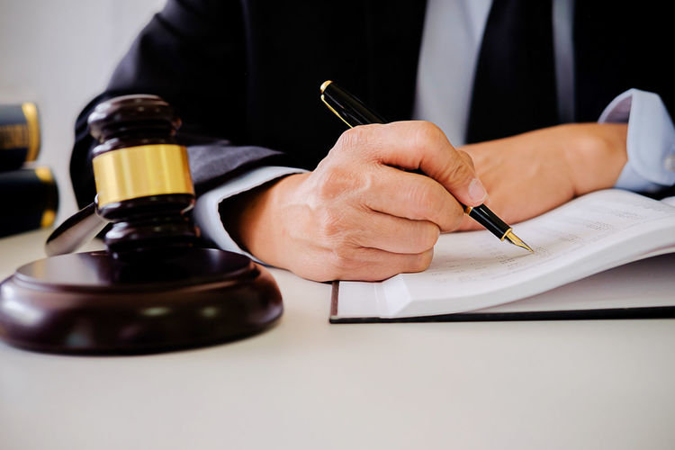 Cropped hand of lawyer writing in book at courtroom