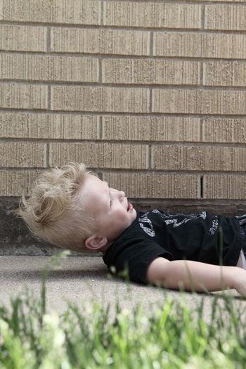 Fallen boy crying on footpath against brick wall