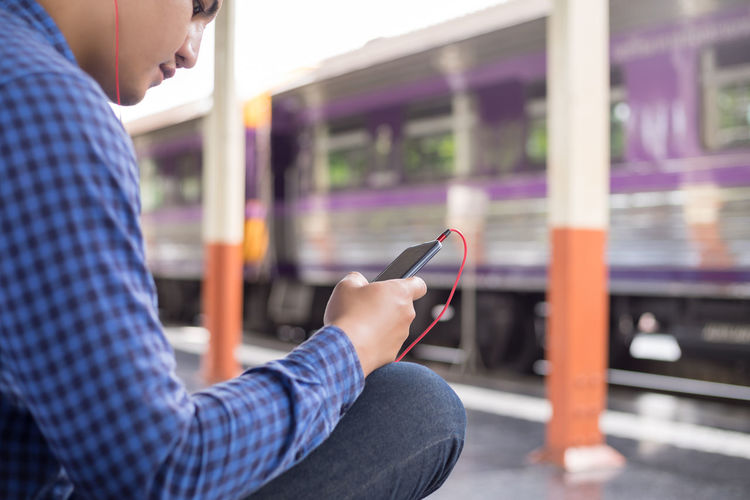Side view of man using mobile phone while sitting at railroad station platform