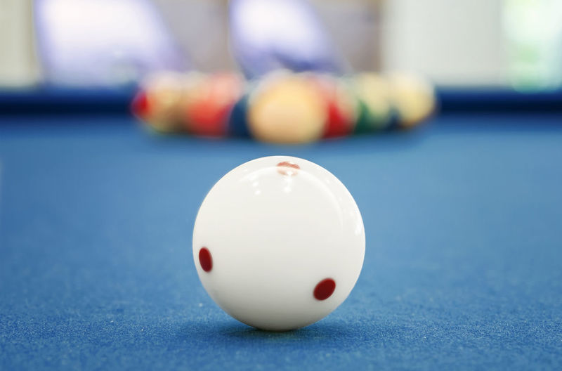 Close-up of white pool ball on table