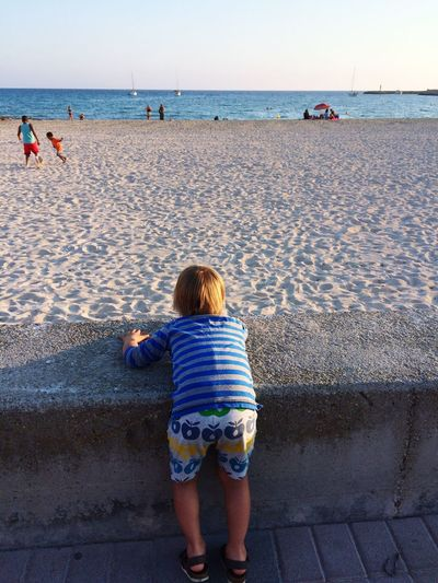 My son admiring the child playing the ball at the beach Hanging Out Beach Seawall Day At The Beach Dayatthebeach Mallorca Shortpants Original Experiences Children Spontaneous Moments Spontaneous Miles Away