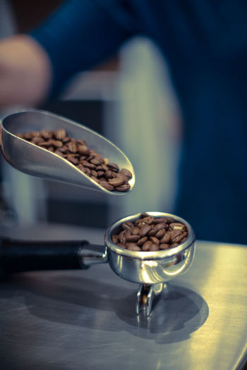 Close-up of roasted coffee beans in serving scoop