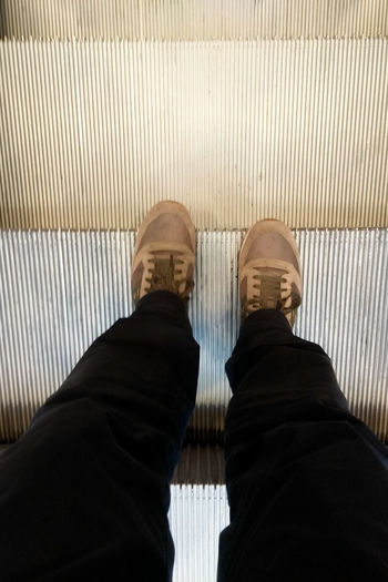 Ascending on the escalator Escalator Stairs Low Section Standing Men Human Leg Shoe Personal Perspective Human Foot Footwear Feet Human Pants Human Feet Flip-flop Flat Shoe Pair Canvas Shoe