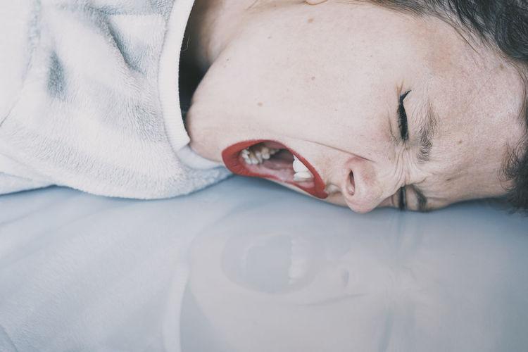 Close-up portrait of teenage boy sleeping on bed