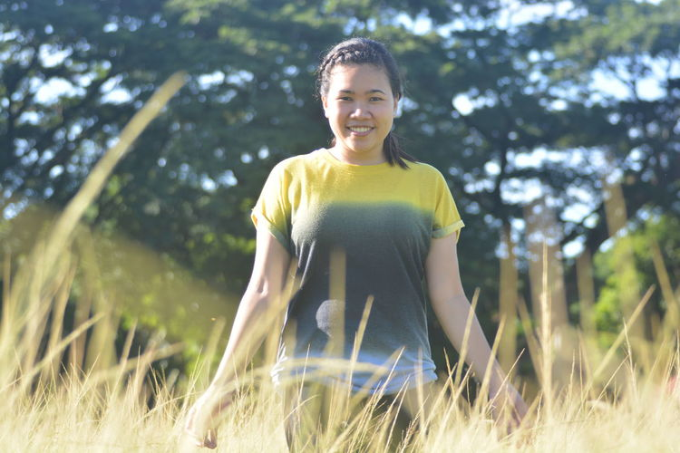 Portrait Of Smiling Woman Standing On Grassy Field Against Trees