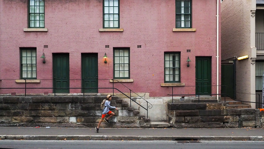 Full length of man running on street against building