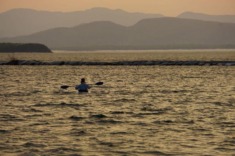 Man rowing boat in lake during sunset