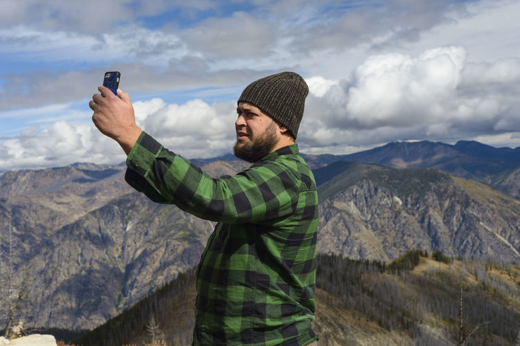 Full length of young man photographing on mountain against sky