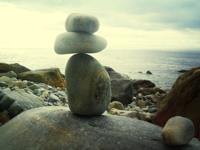 Close-up of stone stack on shore at beach